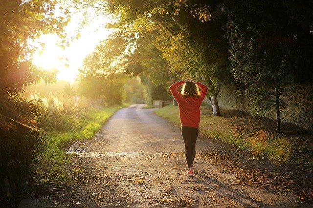 Frau geht im Wald spazieren, Sonnenstrahlen